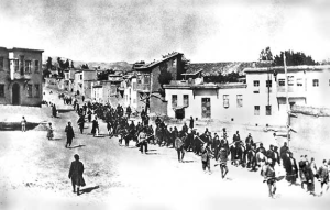 Turkish soldiers march Armenians to prison in Mezireh, April 1915, photographed by an unknown German bystander (Courtesy Wikimedia Commons).