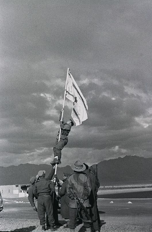 Raising the new flag of the State of Israel, drawn in ink, at The ink-drawn national flag of Israel flies at Um Rashrash (now Eilat), 1949, Misha Achad (Courtesy Wikimedia Commons)