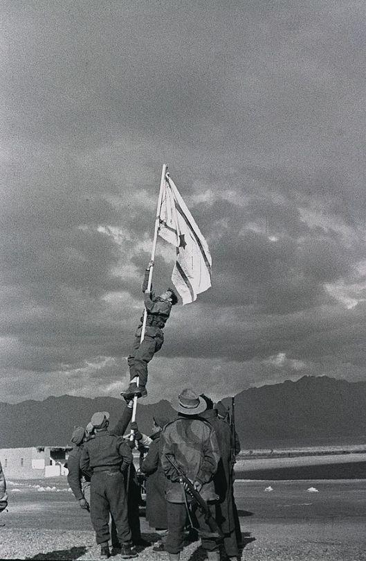 Raising the new flag of the State of Israel, drawn in ink, at The ink-drawn national flag of Israel flies at Um Rashrash (now Eilat), 1949, Misha Achad (Courtesy Wikimedia Commons)